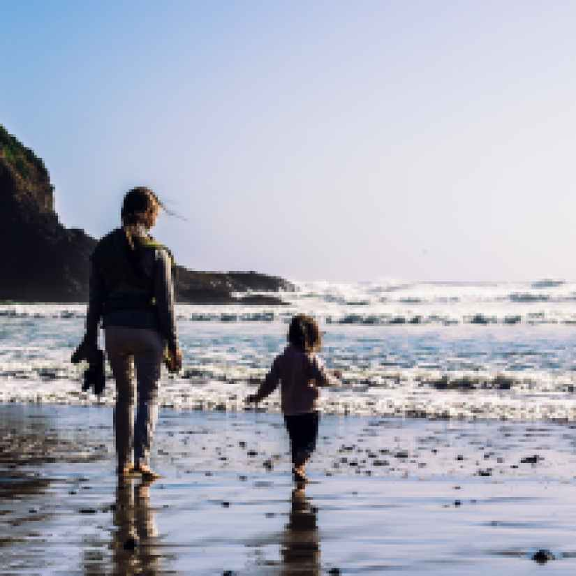 girl and toddler walking at the shore