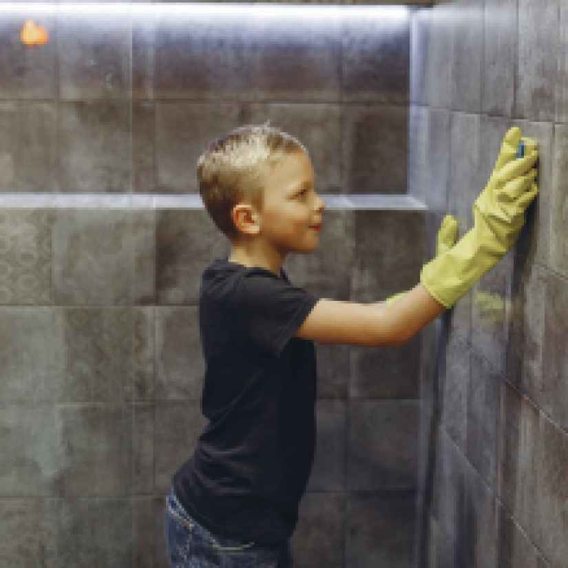 small child washing tiles in bathroom alone