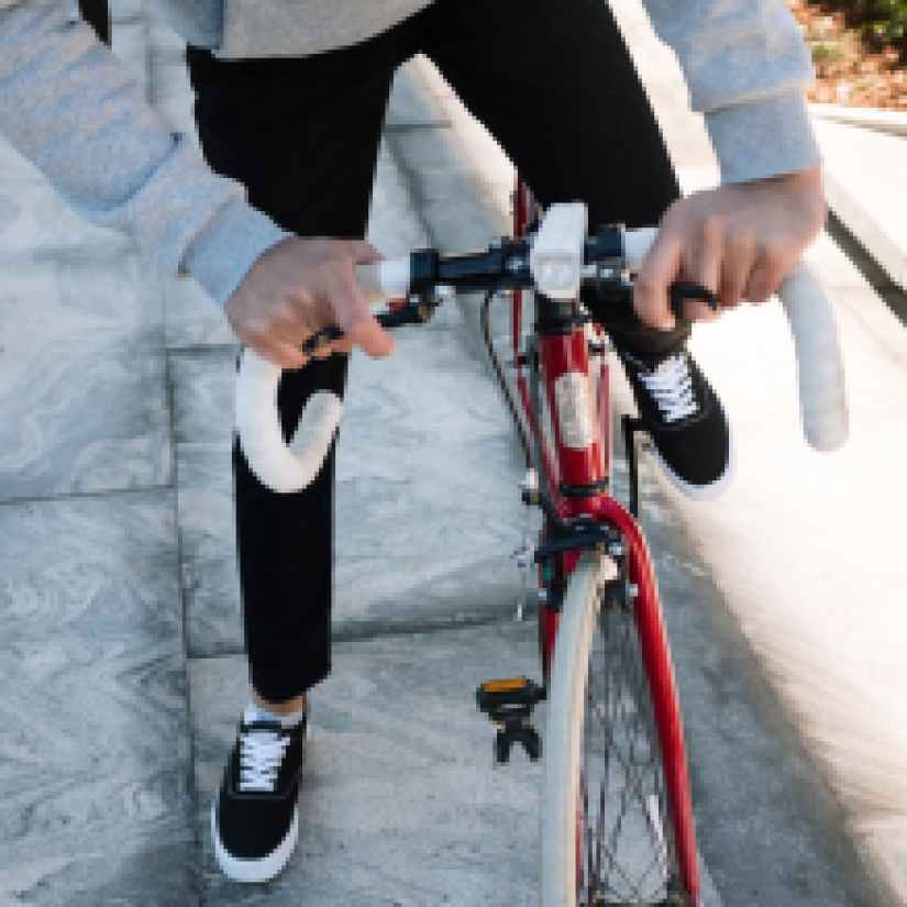 person in black jacket and black pants riding red bicycle