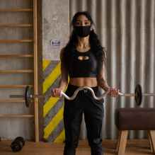 sportswoman in mask training with weights in gym